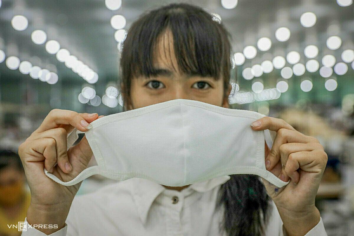 Công nhân Công ty cổ phần Đầu tư & Thương mại TNG sản xuất khẩu trang vải kháng khuẩn. Ảnh: Ngọc Thành