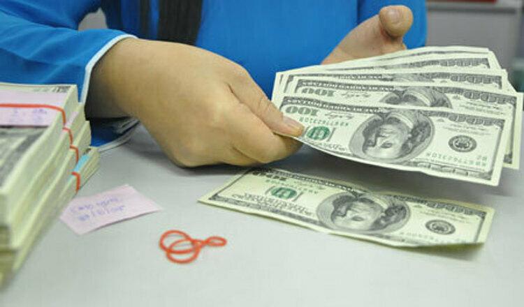 Giao dịch USD tại một ngân hàng thuonwg mại ở TP HCM. Ảnh: Lệ Chi.