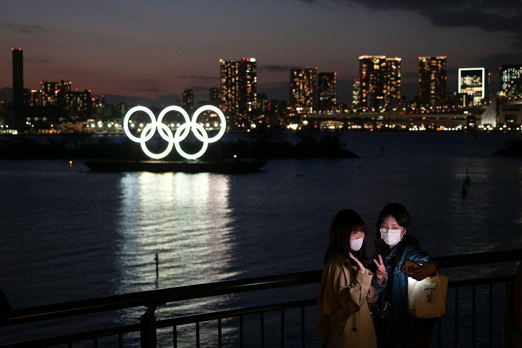 Người dân chụp ảnh với biểu tượng Olympic tại Tokyo. Ảnh: AP
