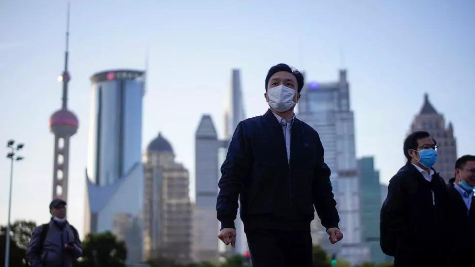 Người dân Trung Quốc đeo khẩu trang tại khu tài chính Lujiazui ở Thượng Hải ngày 19/3. Ảnh: Reuters