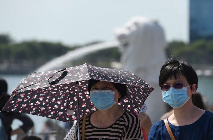 Hai du khách đeo khẩu trang ởMarina Bay (Singapore). Ảnh:AFP