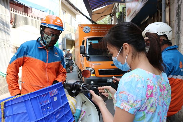 Lê Văn Lộc (bên trái) cùng đồng nghiệp tạm thời gác lại đam mê cầm micro để làm shipper cho AhaMove. Ảnh: Thanh Thu