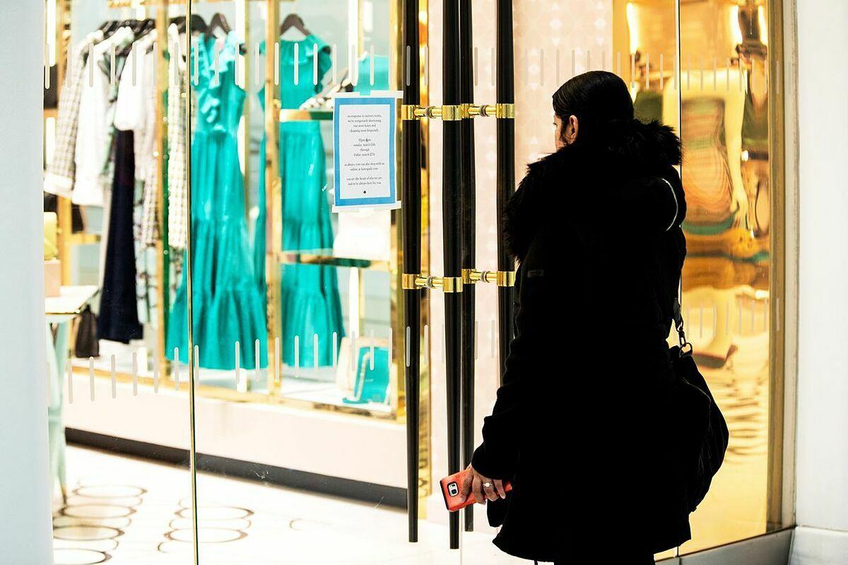 Một khách hàng đọc thông báo dán bên ngoài cửa hàng của Kate Spade & Co đã đóng. Ảnh: WSJ