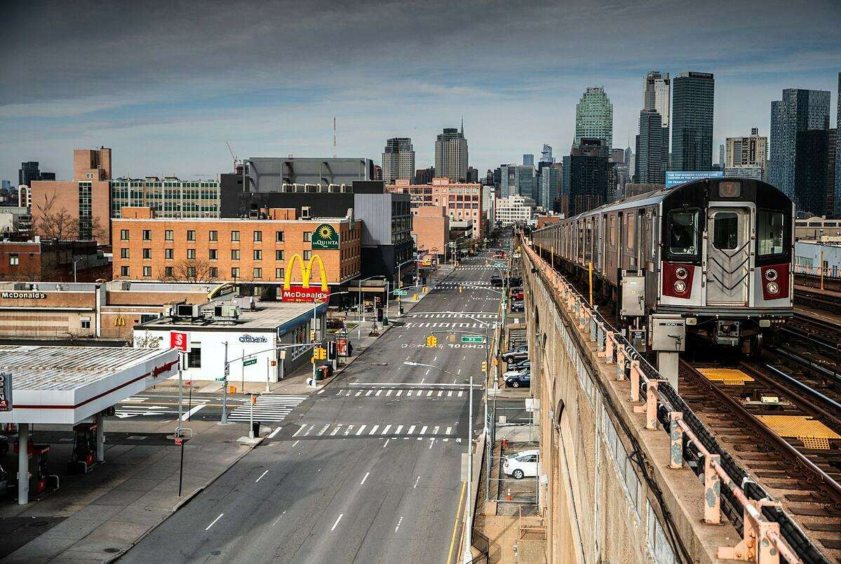 Tàu hỏa đi qua những con phố vắng vẻ tại Queens (New York City, Mỹ). Ảnh: NYT