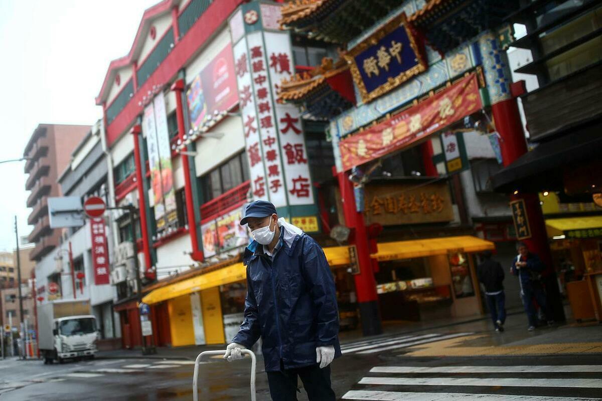 Người dân đi lại trên con phố vắng vẻ tại khu China Town ở Yokohama (Nhật Bản). Ảnh: Reuters