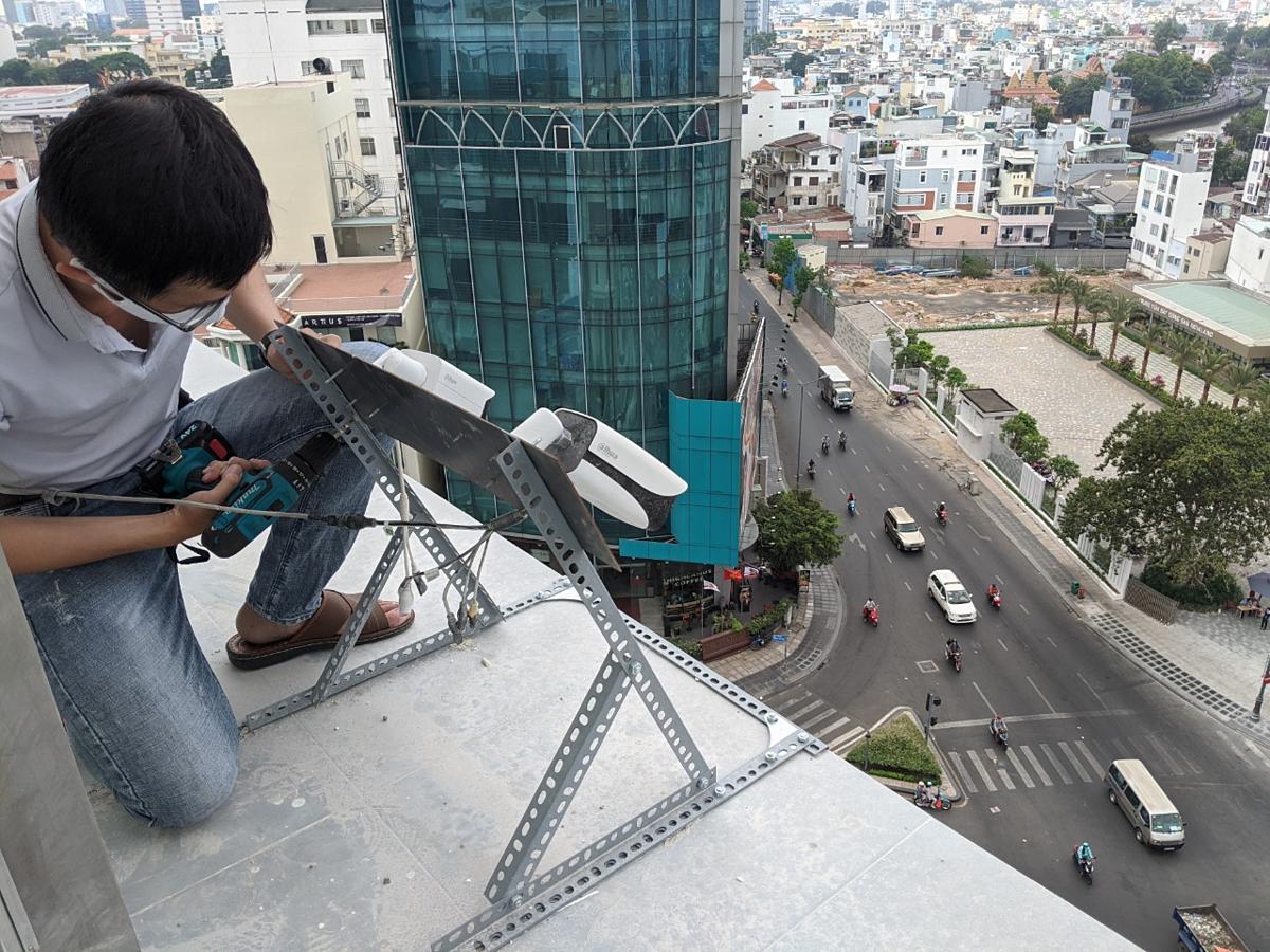 Kỹ thuật viên Compass Tech lắp camera đo lưu lượng tiếp cận bảng quảng cáo.