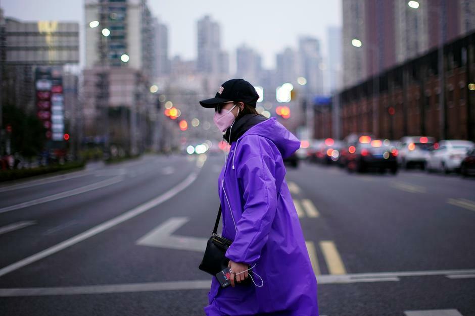 Một phụ nữ đi lại trên đường phố Thượng Hải (Trung Quốc) cuối tháng 2. Ảnh: Reuters