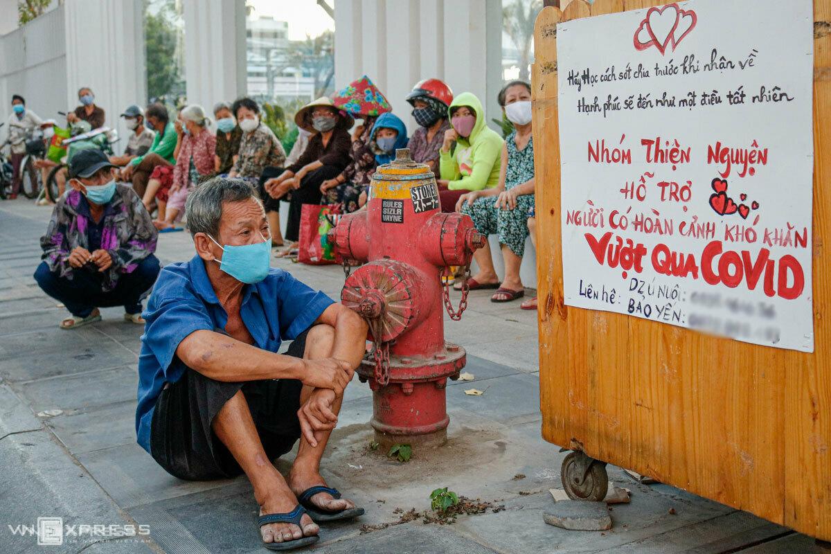 Những người dân có hoàn cảnh khó khăn ngồi chờ nhận quà từ một nhóm từ thiện trên đường Lý Chính Thắng (quận 3, TP HCM) chiều 3/4. Ảnh:Nguyệt Nhi.