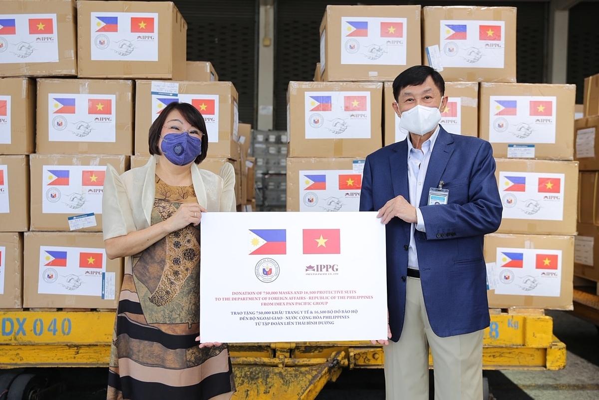 Ông Johnathan Hạnh Nguyễn đại diện QuỹVì cộng đồng IPPG trao biểu trưng vật dụng y tếđến bà Lê ThịPhụng -Tổng lãnh sựdanh dựPhilippinestại TP HCM.