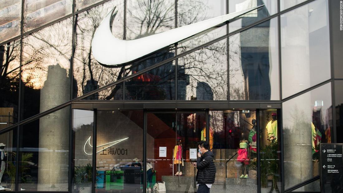 Một người đeo khẩu trang đi qua một cửa hàng của Nike tại Thượng Hải, Trung Quốc vào tháng 3/2020. Ảnh: CNN