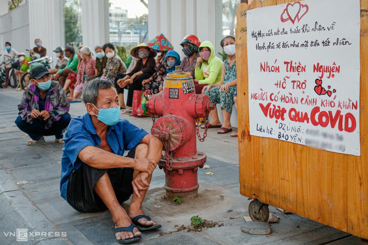 Những người dân có hoàn cảnh khó khăn ngồi chờ nhận quà từ một nhóm từ thiện trên đường Lý Chính Thắng (quận 3, TP HCM) chiều 3/4. Ảnh: Nguyệt Nhi.