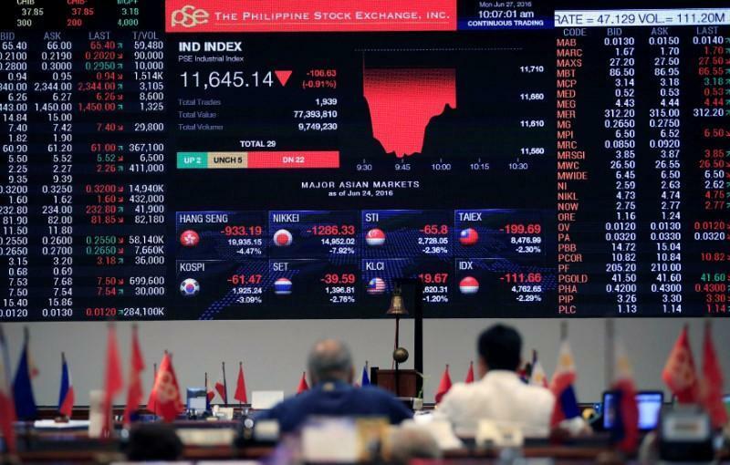 Nhà đầu tư theo dõi bảng điện tử tại Sở giao dịch chứng khoán Philippines. Ảnh: Reuters