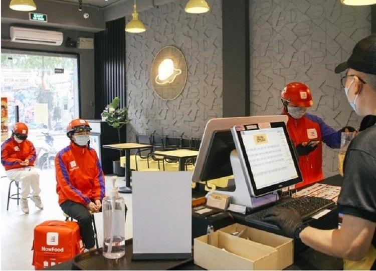 Nhân viên giao hàng Now và nhân viên quán giữ khoảng cách 2m.