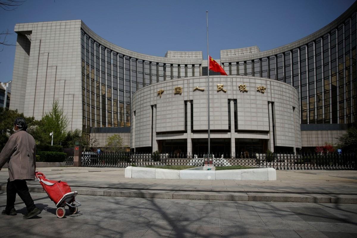 Một người đeo khẩu trang đi ngang qua Ngân hàng Nhân dân Trung Quốc đang treo cờ rũ trong Ngày tưởng niệm những người chết vì Covid-19 hôm 4/4. Ảnh: Reuters