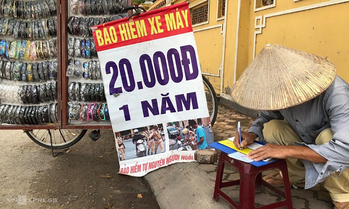 Một bán kính măt, kiêm bán bảo hiểm xe máy viết giấy chứng nhận cho khách tại lề đường Hồ Tùng Mậu trưa 18/5. Ảnh: Anh Tú