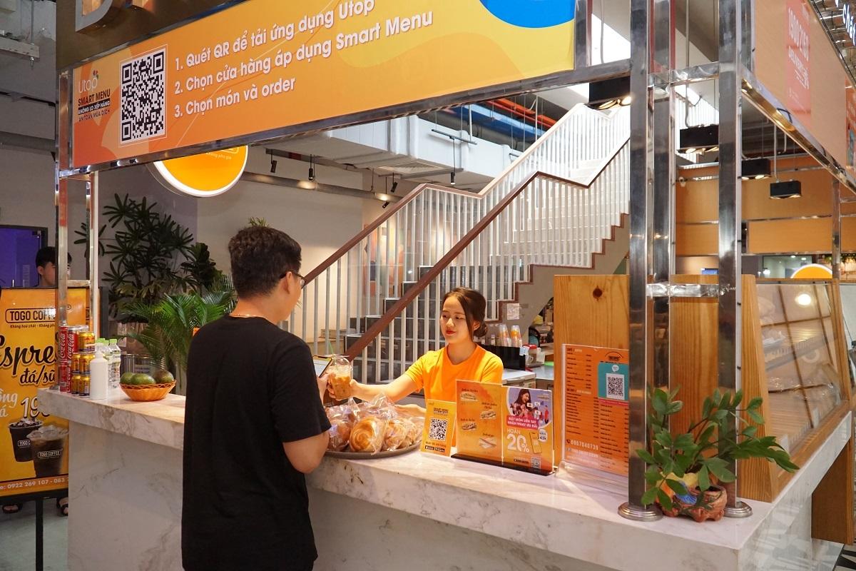 Nhân viên quán giao món cho khách hàng sử dụng tính năng Smart Menu trên Utop.