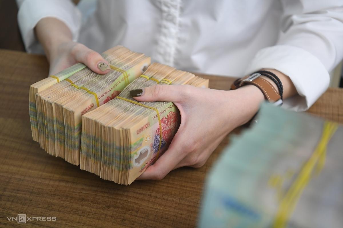 Nhân viên một ngân hàng thương mại tại Hà Nôi kiểm đếm tiền. Ảnh: Giang Huy.