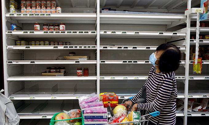Kệ hàng một siêu thị gần như trống trơn tại Singapore. Ảnh:Reuters