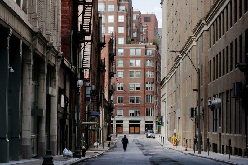 Người đi bộ trên một con phố vắng vẻ vì đại dịch tạiMassachusetts. Ảnh: Reuters