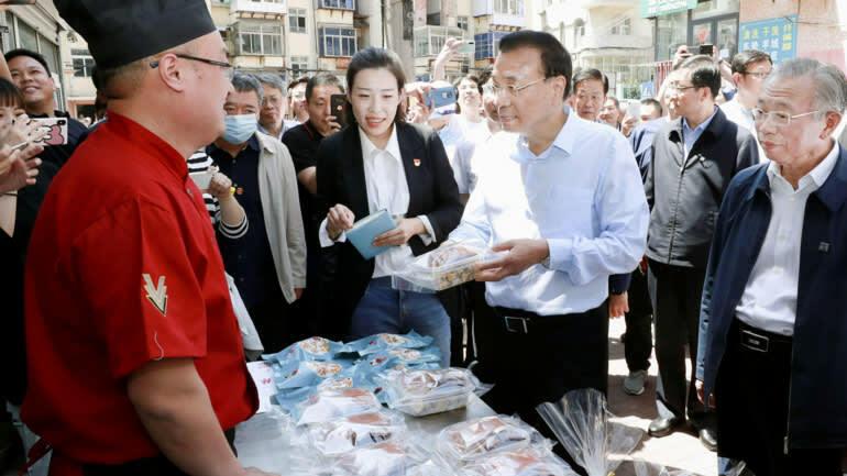 Thủ tướng Trung Quốc Lý Khắc Cường thăm các quầy hàng rong ở Sơn Đông. Ảnh: Kyodo