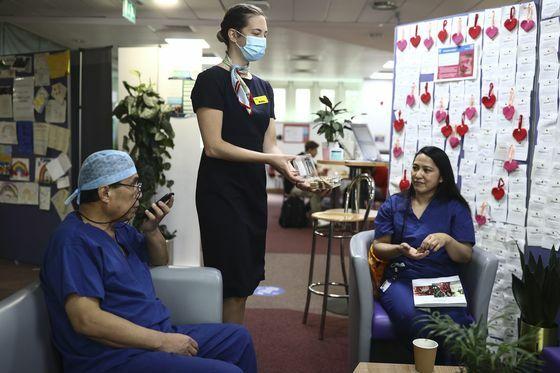 Một tiếp viên hàng không phục vụ nhân viên y tế tại Bệnh việnWhittington. Ảnh: Bloomberg