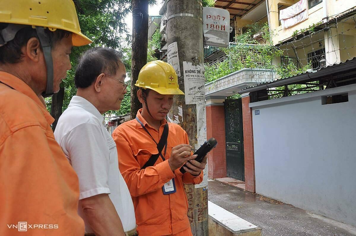 Nhân viên ngành điện đo công tơ điện tử bằng thiết bị đo từ xa sáng 25/4. Ảnh:Anh Minh.
