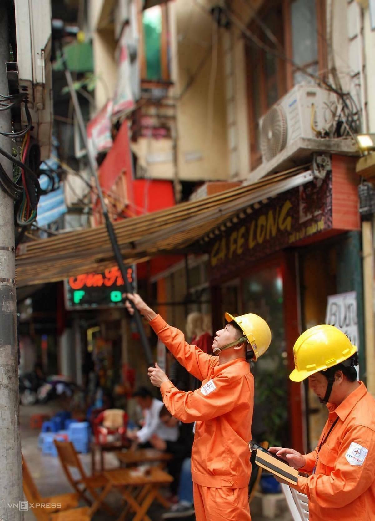 Công nhân điện lực Hà Nội ghi chỉ số điện tại khu vực còn sử dụng công tơ cơ, bằng camera và phần mềm máy tính bảng. Ảnh: Anh Minh