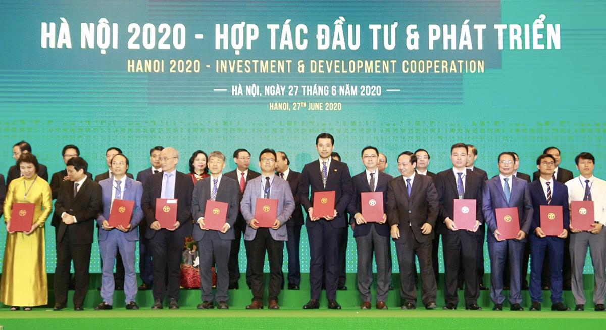 Ông Đỗ Hoàng Việt – Phó TGĐ Tập đoàn Tân Hoàng Minh (đứng giữa) nhận biên bản ghi nhớ cam kết đầu tư dự án khu Outlet tại huyện Đông Anh.