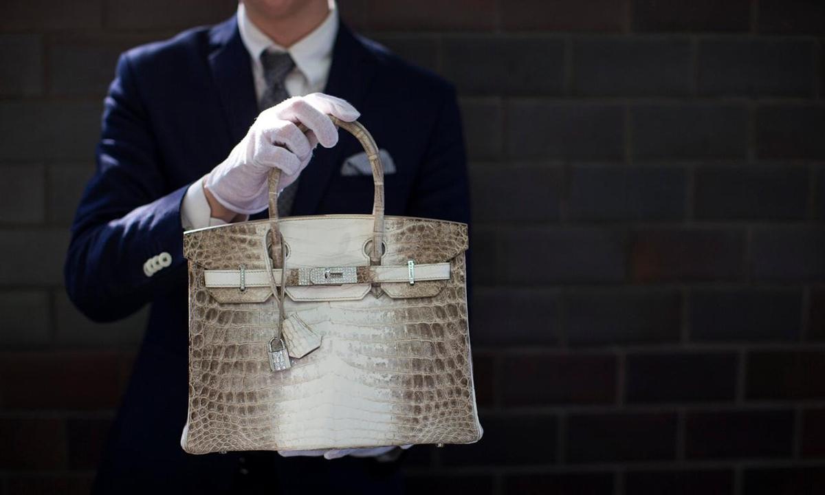 Một mẫu túi Birkin trên tay nhân viên Hermes tại một phiên đấu giá năm 2014. Ảnh: Reuters