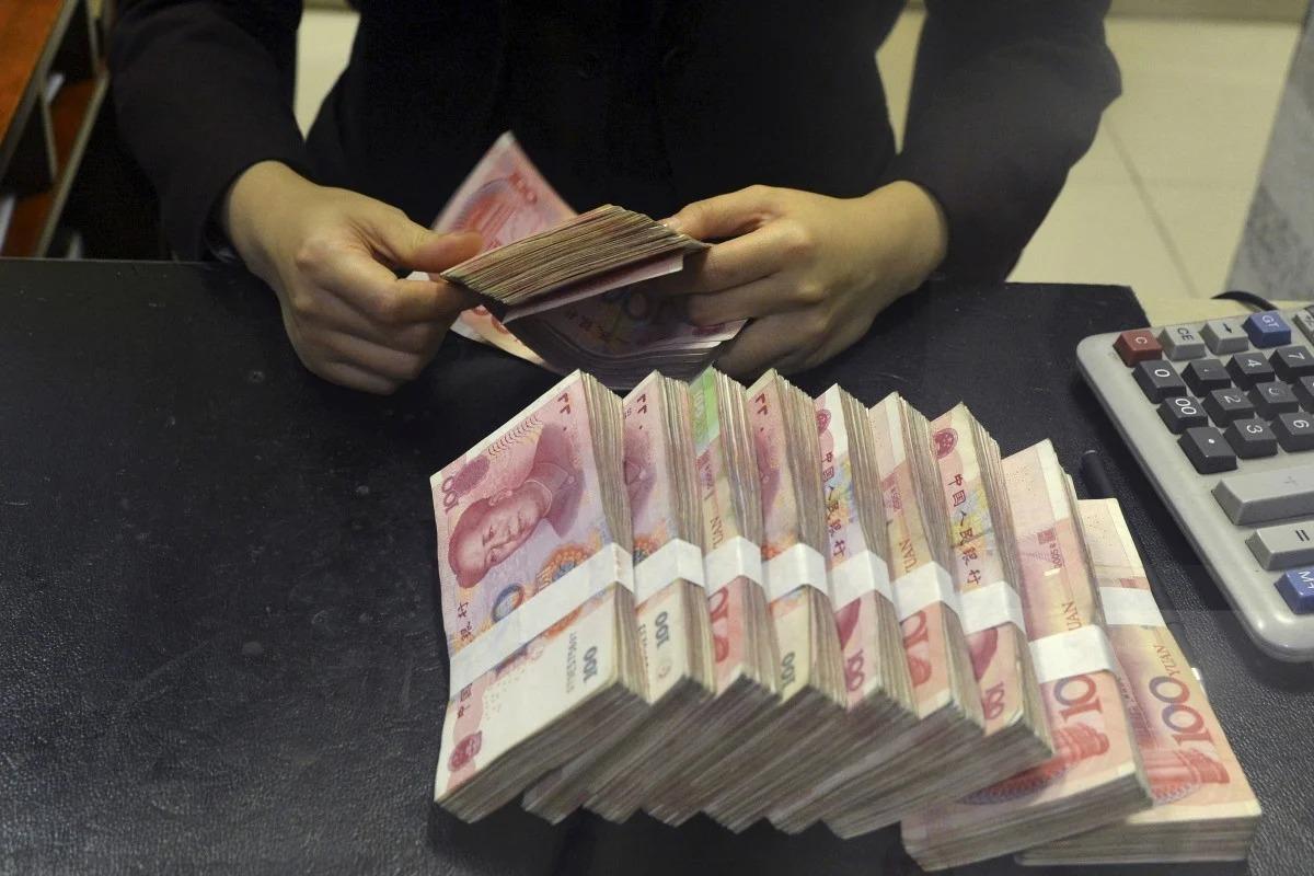 Giao dịch tiền mặt tại một ngân hàng ở Trung Quốc. Ảnh: Reuters