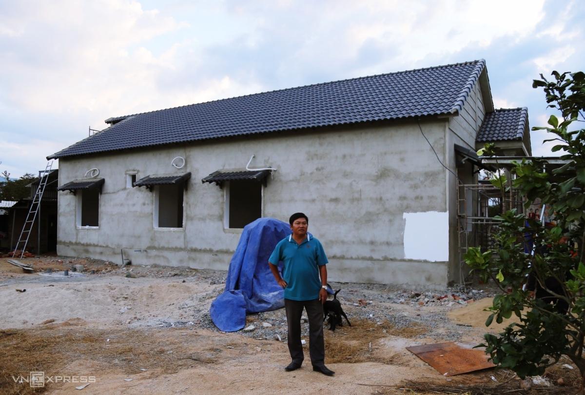 Ông Hiểu bên cạnh ngôi nhà đang xây cho mẹ vợ. Ảnh: Xuân Ngọc.