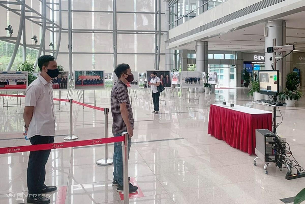 Nhân viên và khách tới làm việc tại EVN được đo thân nhiệt ngày 27/7. Ảnh: Anh Minh.