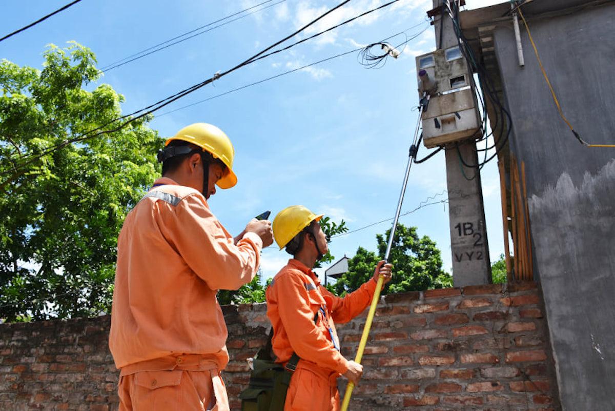 Công nhân Công ty Điện lực Mê Linh ghi chỉ số điện trên địa bàn huyện Mê Linh (Hà Nội). Ảnh: Anh Minh