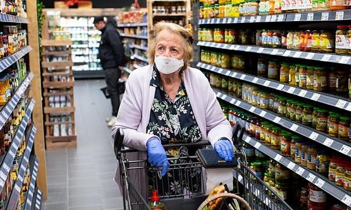 Một khách hàng đeo khẩu trang và găng tay đi siêu thị tại Đức. Ảnh: Hoppe