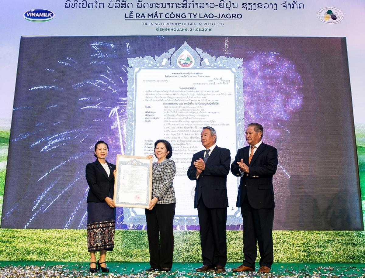 Bà Mai Kiều Liên nhận giấy chứng nhận đầu tư cho dự án Tổ hợp trang trại bò sữa Lao - Jagro từ Thứ trưởng Bộ Kế hoạch và Đầu tư Lào. Ảnh: Vinamilk.