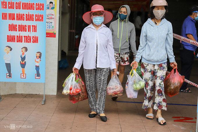 Nhiều bà nội trợ tay xách đầy thịt cá, chuẩn bị cho việc ba ngày tới mới được đi chợ tiếp. Ảnh: Nguyễn Đông.