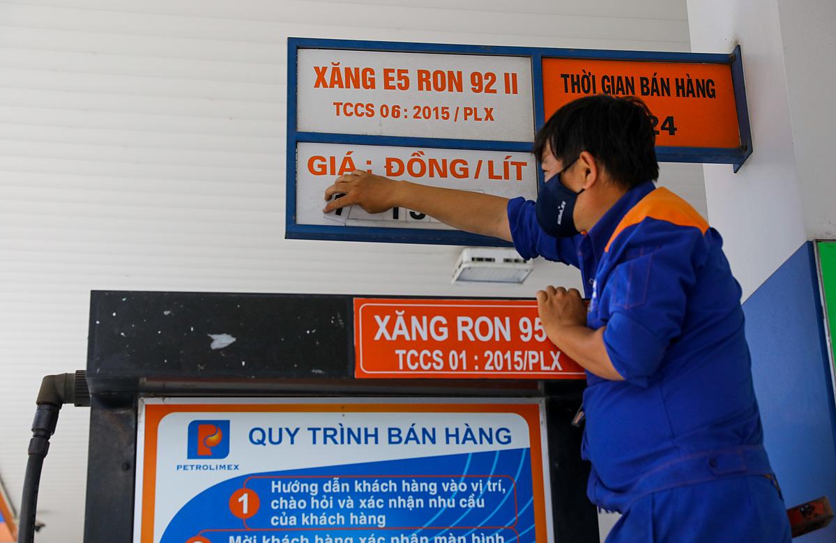 Nhân viên cây xăng điều chỉnh giá tại cửa hàng quận 1. TP HCM. Ảnh: Quỳnh Trần.