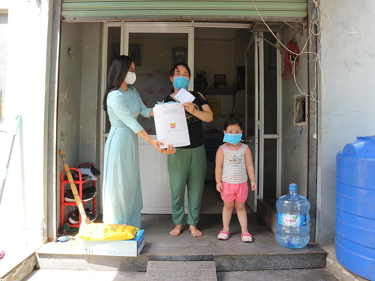 Đại diện Tập đoàn VinaCapital (bên trái) trao phần quà hỗ trợ cho gia đình trẻ mắc bệnh tim bẩm sinh.