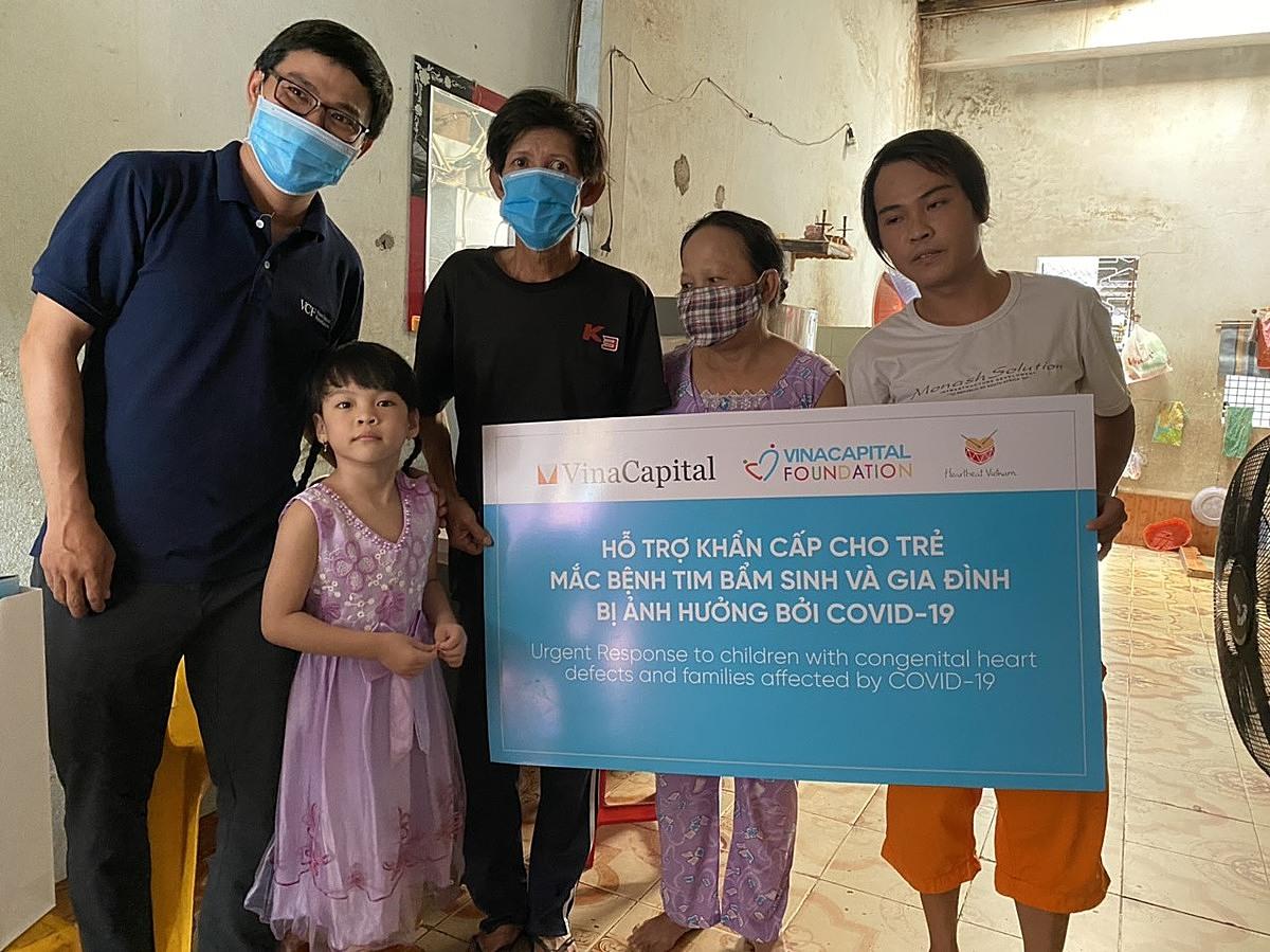 Đại diện VinaCapital Foundation (từ trái sang) trao phần quà hỗ trợ cho gia đình trẻ mắc bệnh tim bẩm sinh.