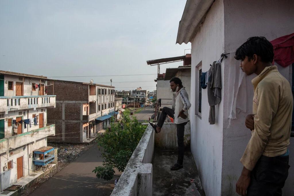 [Sanjay Singh, một chân đặt lên vách ban công, là một lao động nhập cư từ Madhya Pradesh, vừa quay lại Surat gần đây. Ảnh: NYT
