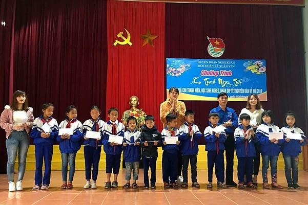 Chị Hoàng Thảo (phía sau) đại diện công ty trao quà cho các em học sinh nghèo.