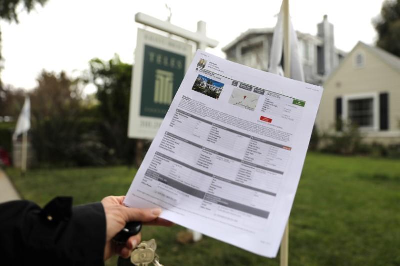 Một phụ nữ cầm tờ quảng cáo bán nhà tại California (Mỹ). Ảnh: Reuters