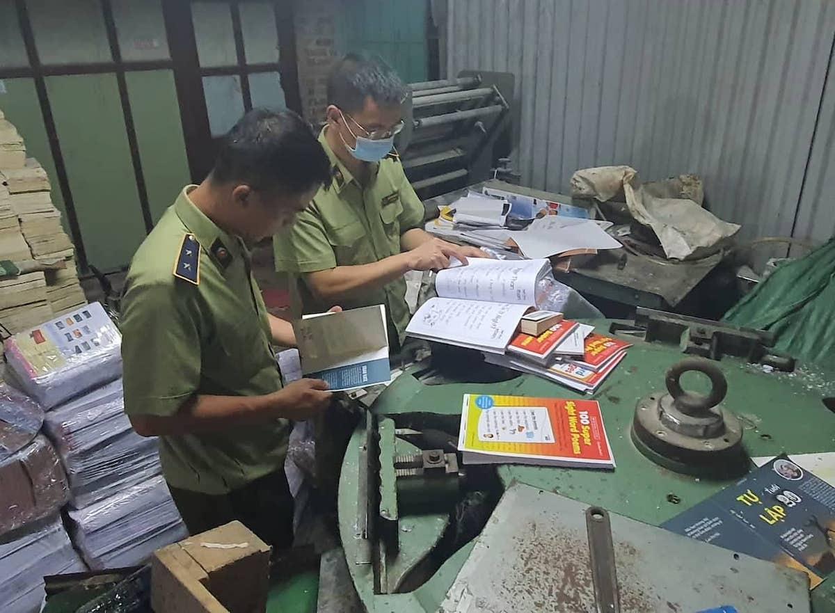 Cán bộ quản lý thị trường kiểm tra sách nghi in lậu tại cơ sở kinh doanh ở quận Nam Từ Liêm, Hà Nội, ngày 15/9. Ảnh: Quản lý thị trường Hà Nội.