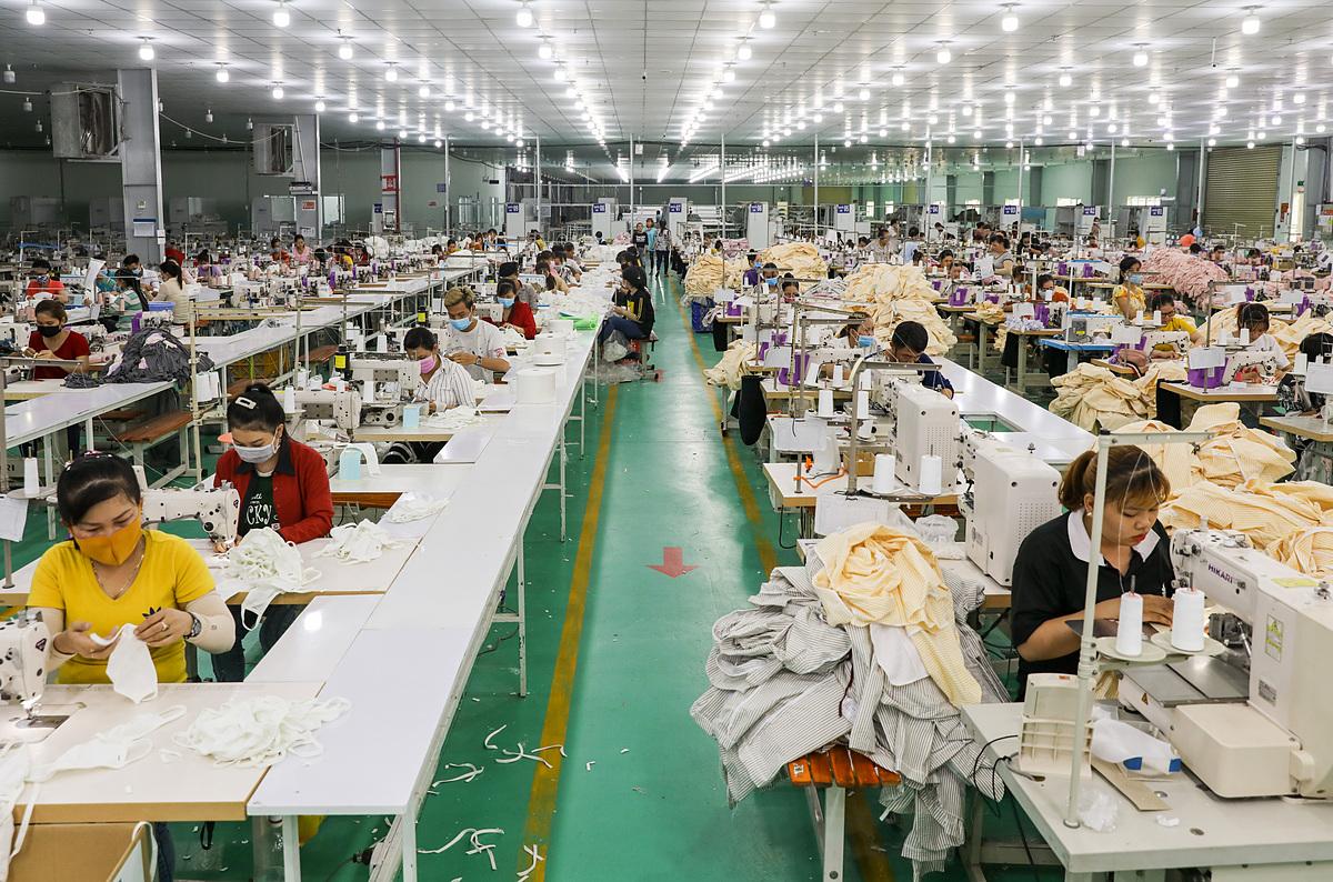 Công nhân của Công ty GarmentTech Pro (Khu công nghiệp Tân Đô, huyện Đức Hoà, Long An) sản xuất khẩu trang vải. Ảnh: Quỳnh Trần.