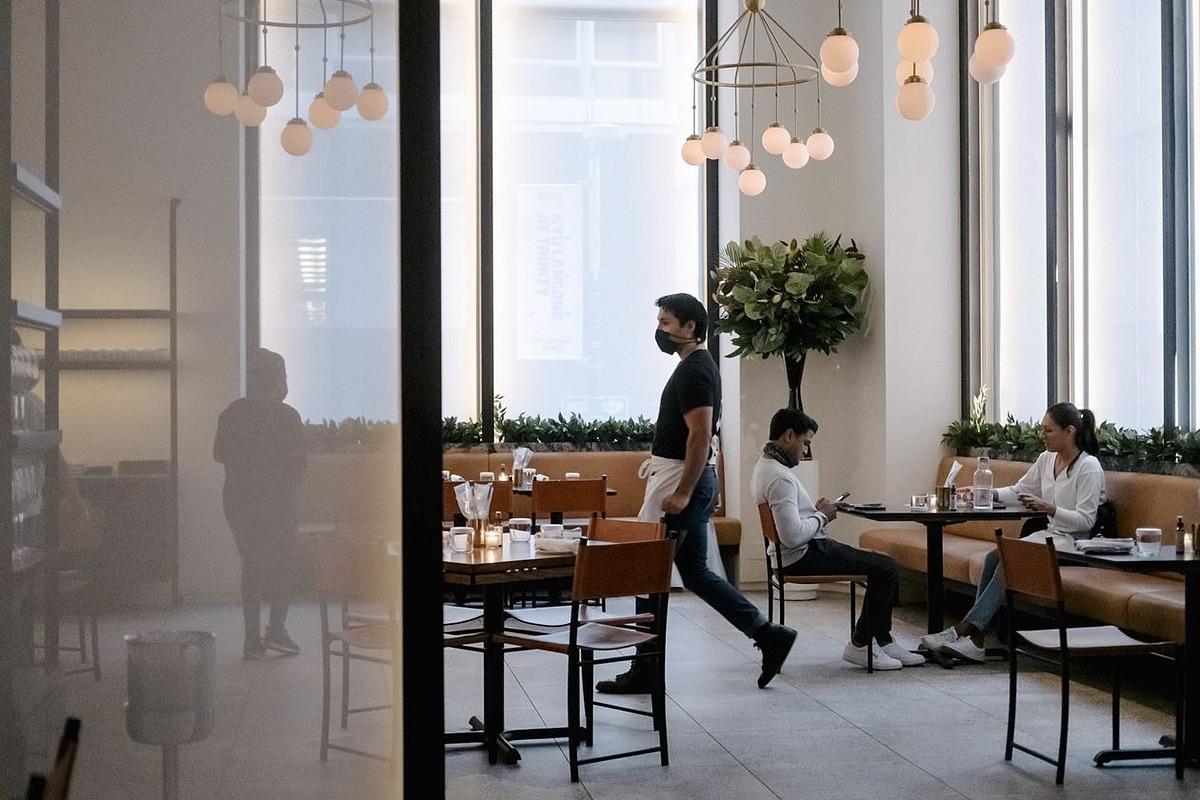 Nhân viên phục vụ đeo khẩu trang tại một nhà hàng ở Mỹ. Ảnh: Bloomberg