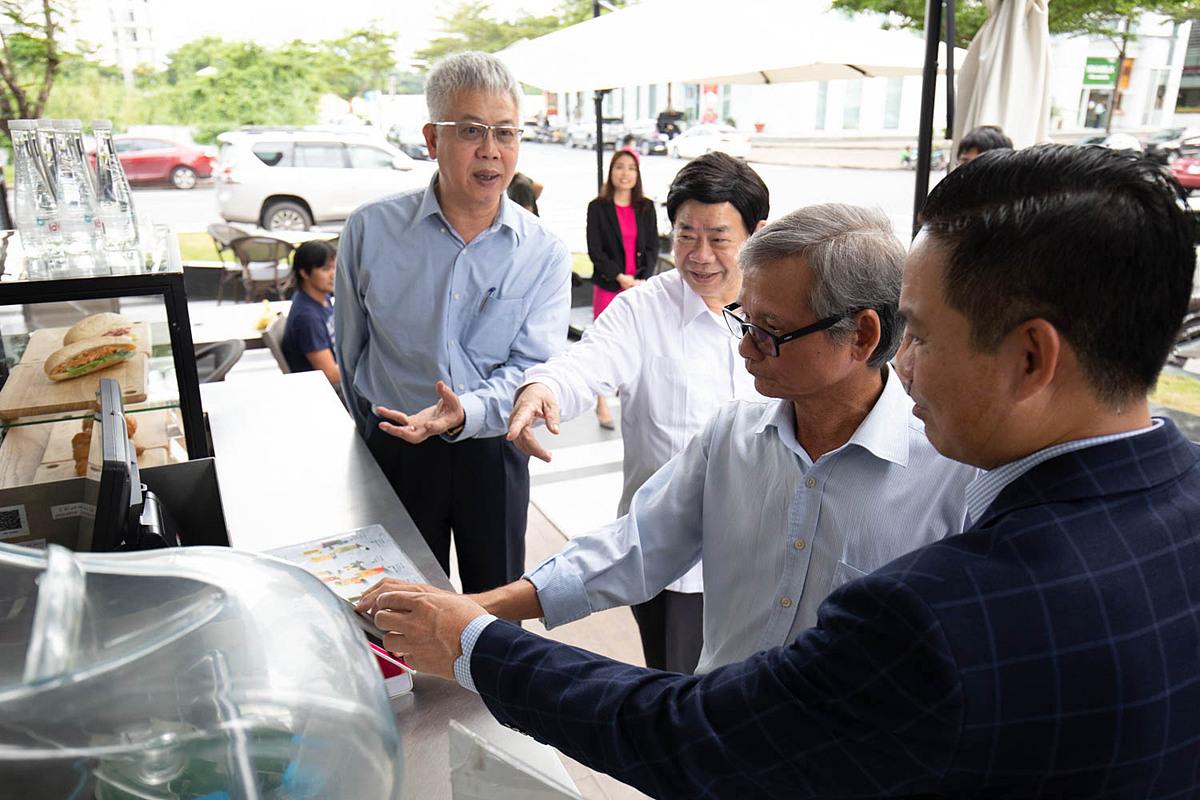 Ông Nguyễn Đức Kiên, Tổ trưởng Tổ tư vấn kinh tế của Thủ tướng Chính phủ (ngoài cùng bên trái) cùng các thành viên tổ tư vấn và lãnh đạo MoMo trải nghiệm thanh toán bằng ví điện tử tại một cửa hàng đồ uống tại quận 7, TP HCM chiều 12/10. Ảnh: Thy Nhật