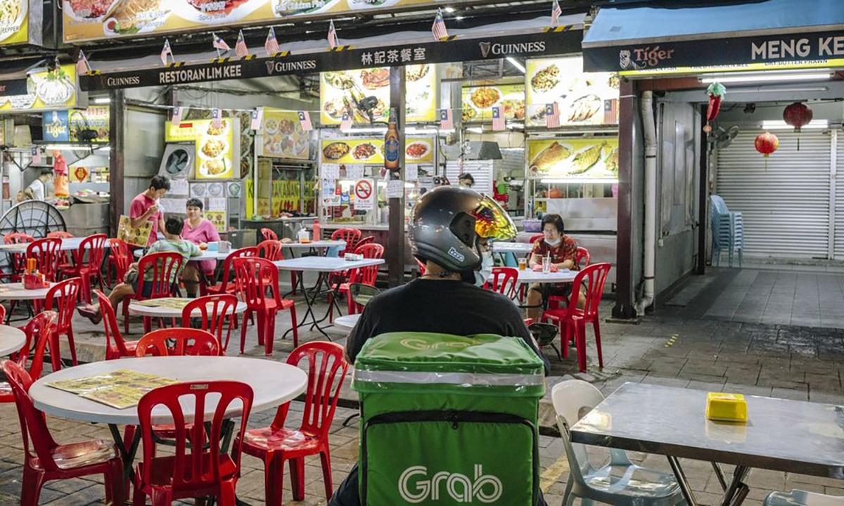 Một tài xế Grab chờ lấy đồ ăn tại Kuala Lumpur. Ảnh: Bloomberg