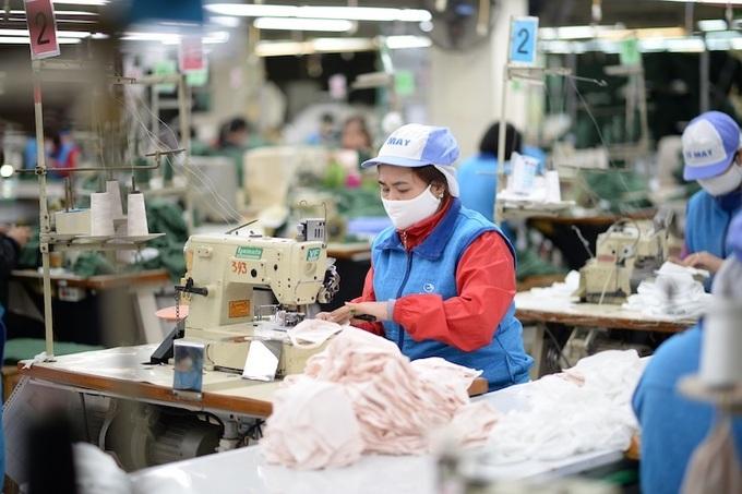 Công nhân công ty Dệt kim Đông Xuân sản xuất khẩu trang vải kháng khuẩn phòng Covid-19. Ảnh: Cao Hưng.