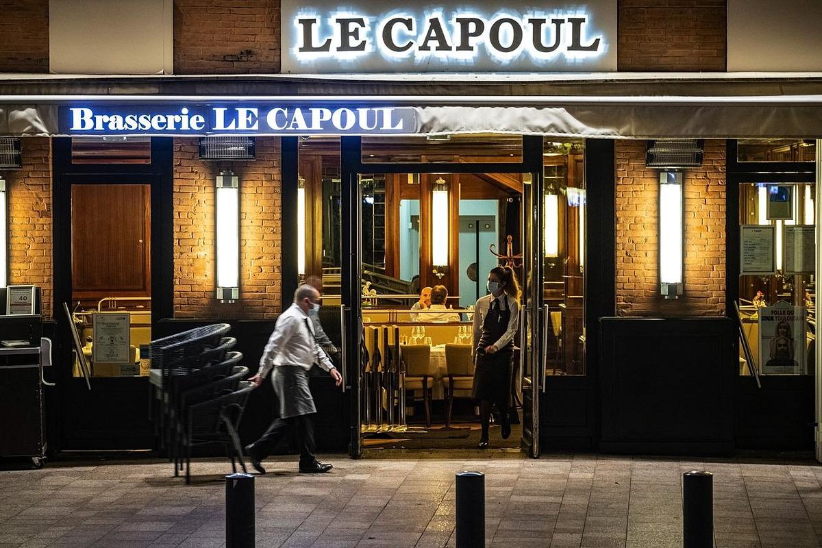 Một người phục vụ dọn những chiếc ghế tại một quán bar trước giờ giới nghiêm ở Toulouse, Pháp. Ảnh: Bloomberg.