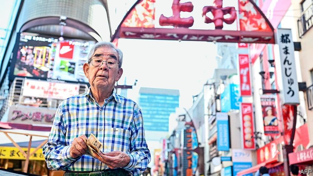Một người cao tuổi cầm tiền mặt trên một con phố mua sắm tại Nhật Bản. Ảnh: AFP.